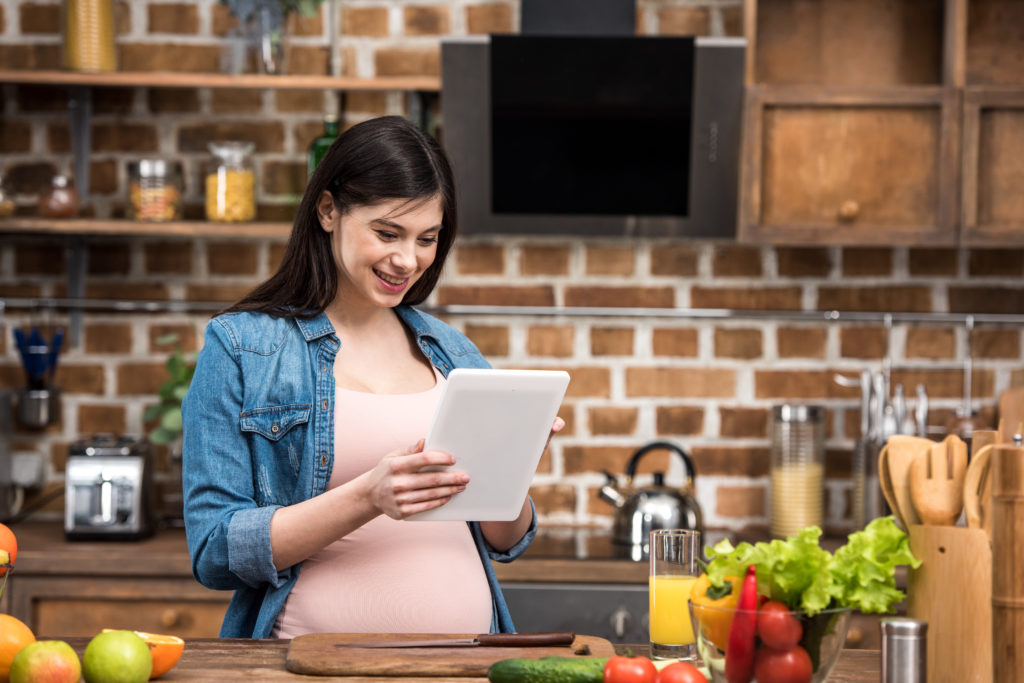 pregnant woman reading tablet in kitchen